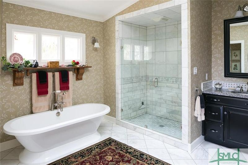 Luxurious Master Bath features Carrara marble floors, gorgeous soaking tub and walk in shower enclosed with glass.