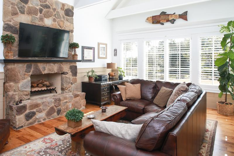 This family room boasts a stone fireplace and a wall of windows.
