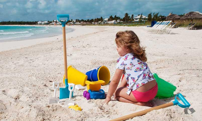 Little girl playing in sand on beach at Grand Isle Resort in Great Exuma, Bahamas
