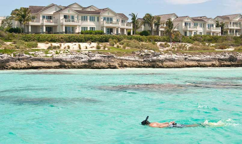 Man snorkeling in front of Grand Isle's Villas in Great Exuma, Bahamas