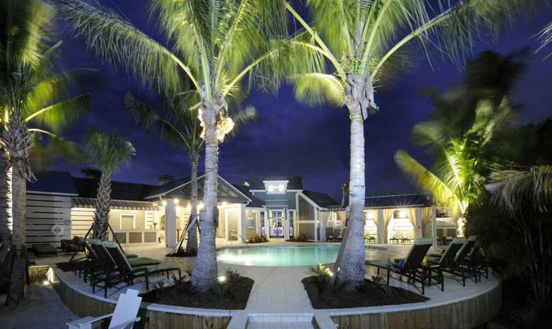 Evening view of the Mangrove Walk pool at Harbour Isle on Anna Maria Sound features new coach model homes, designed in southern coastal resort-style architecture.