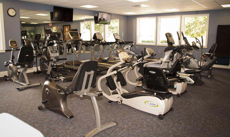 A newly renovated fitness facility has cardiovascular and strength training equipment, locker rooms, and a personal trainer.