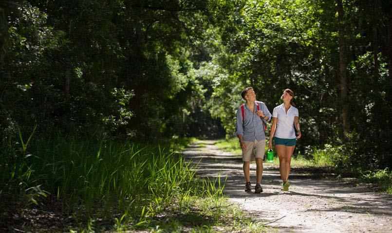 A young couple walking along a nature trail at the Nocatee Preserve.